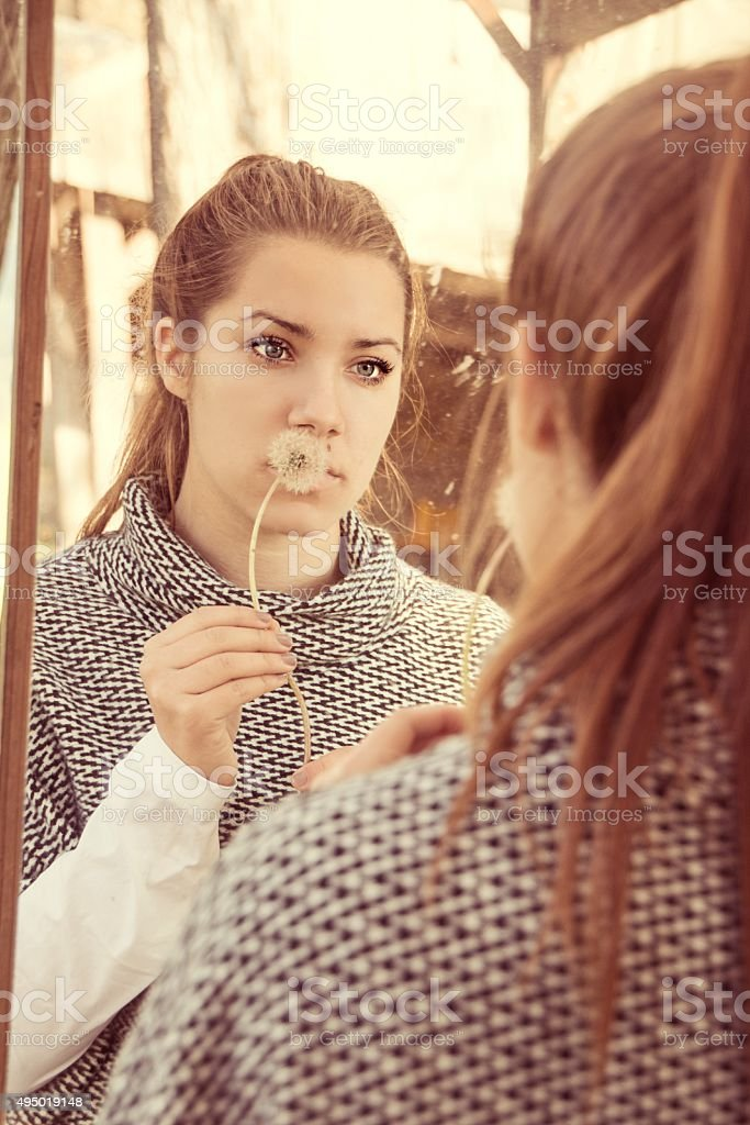 Girl looking in the mirror stock photo
