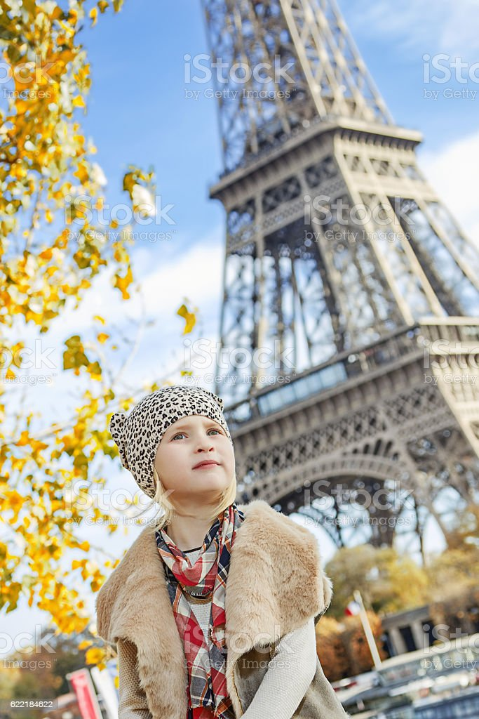 girl looking into distance while sitting on parapet in Paris stock photo