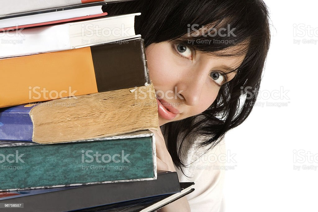 girl looking out from behind a pile of books stock photo