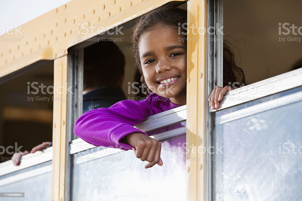 Girl looking out school bus window stock photo