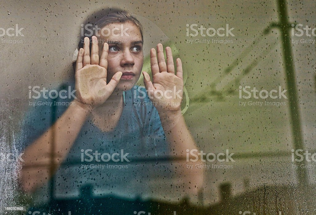 Girl looking out Window (with reflections of the City) royalty-free stock photo