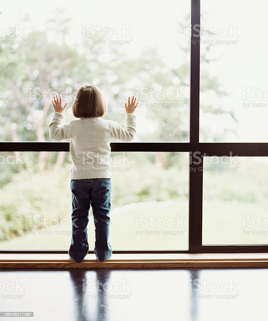 Girl (2-4) looking out window, rear view stock photo