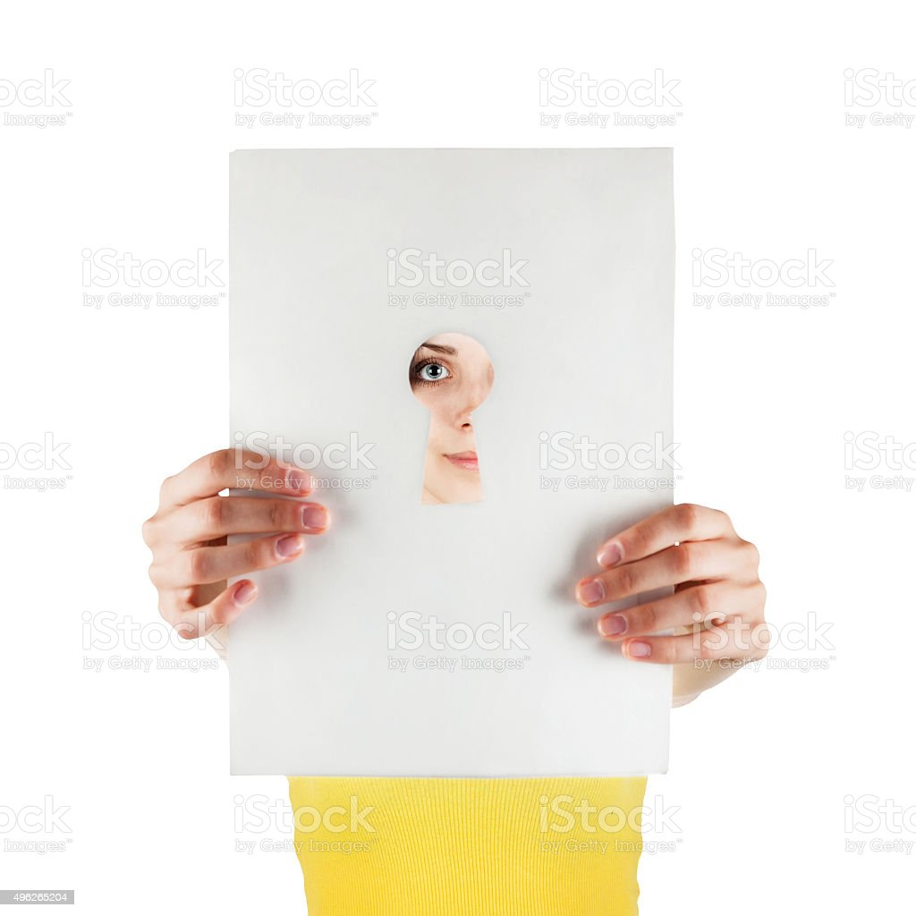 Girl looking through a keyhole stock photo