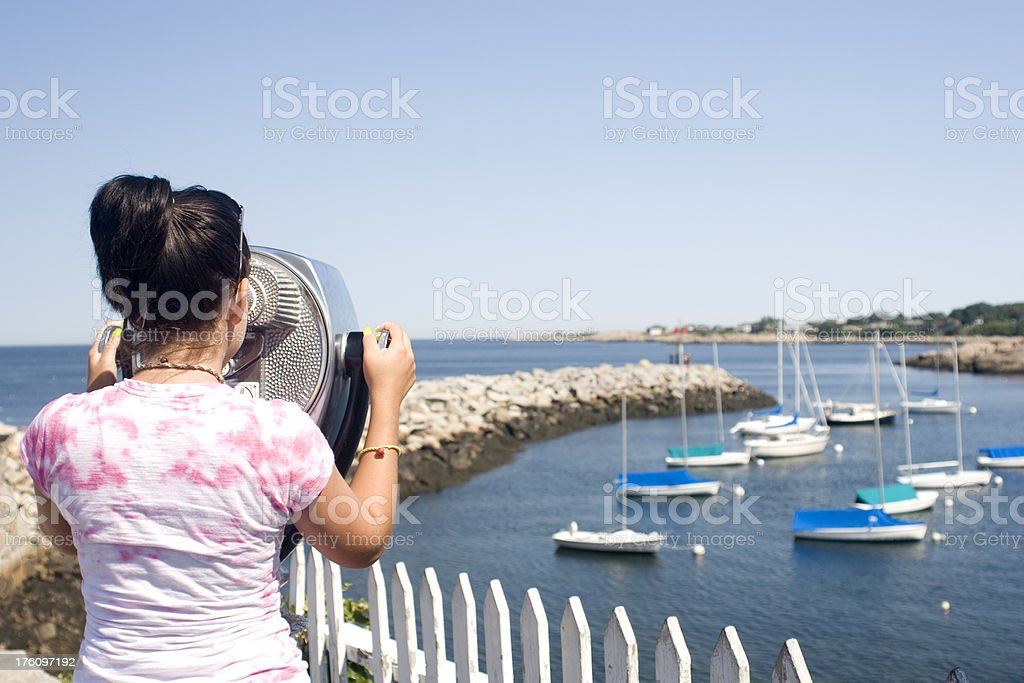 Girl looking through coin operated binoculars stock photo
