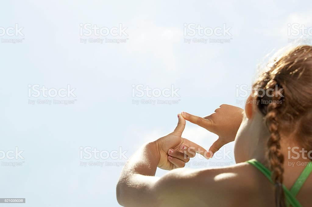 Girl looking through fingers at the sky stock photo