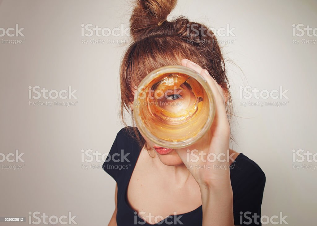 Girl looking through the bottom of empty jars peanut butter. stock photo