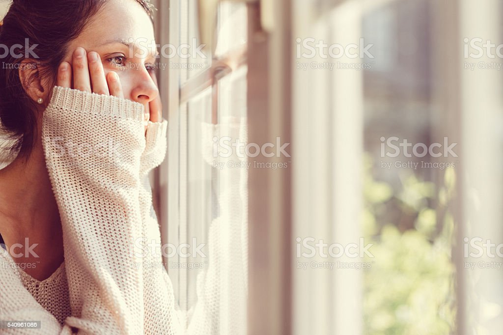 Girl looking through the window stock photo