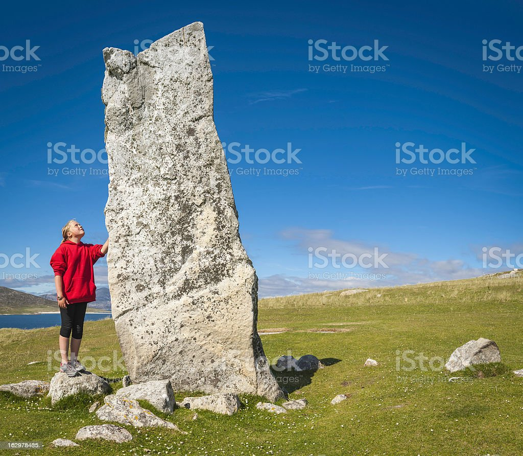 Girl looking up at ancient stone monolith Outer Hebrides Scotland stock photo