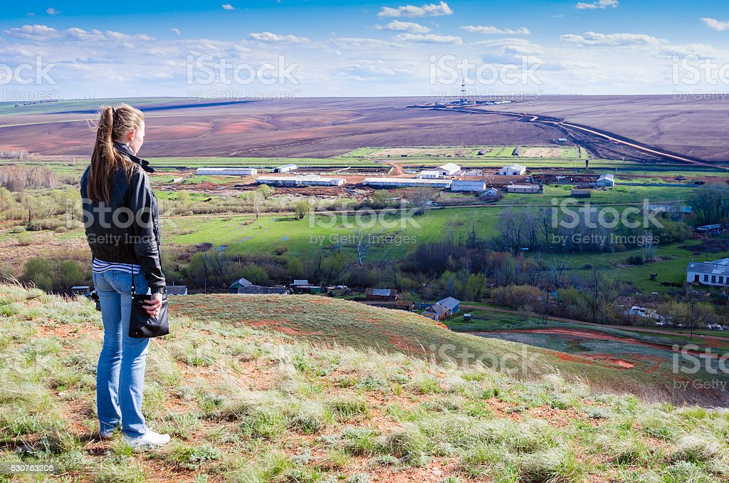Girl looks from hill on rural landscape with drilling rigs stock photo