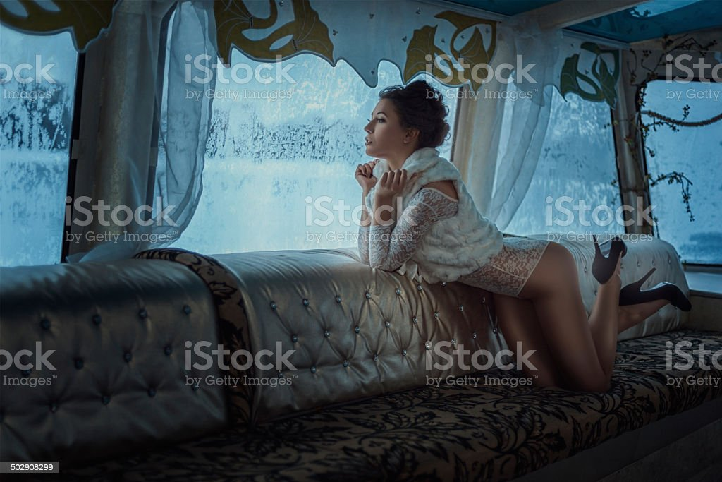 Girl looks in the winter window. stock photo