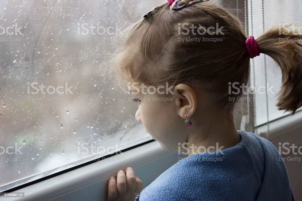 girl looks out of the windows on a rain stock photo