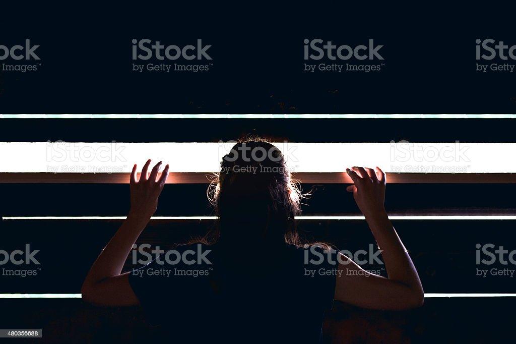 Girl looks outside stock photo