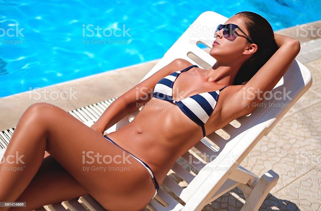 Girl lying and sunbathing by the pool stock photo