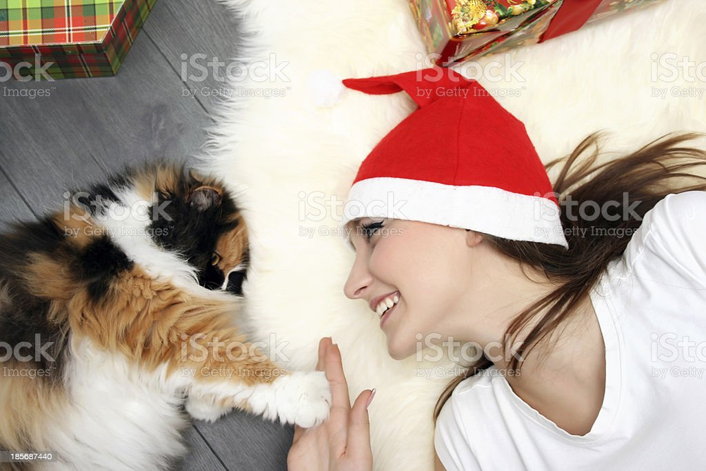 Girl lying at floor in Christmas hat with fluffy cat royalty-free stock photo