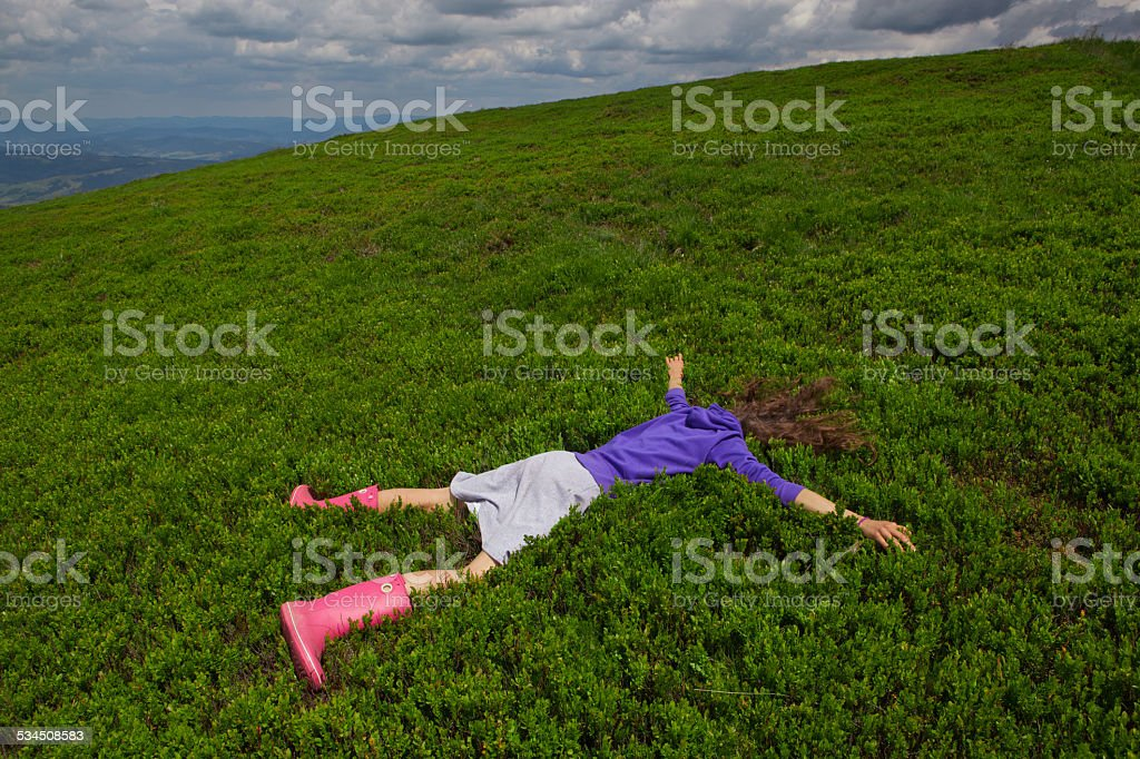 Girl lying facedown on the green bluberry field stock photo