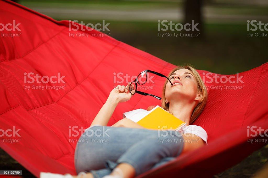 Girl lying in hammock outdoors stock photo
