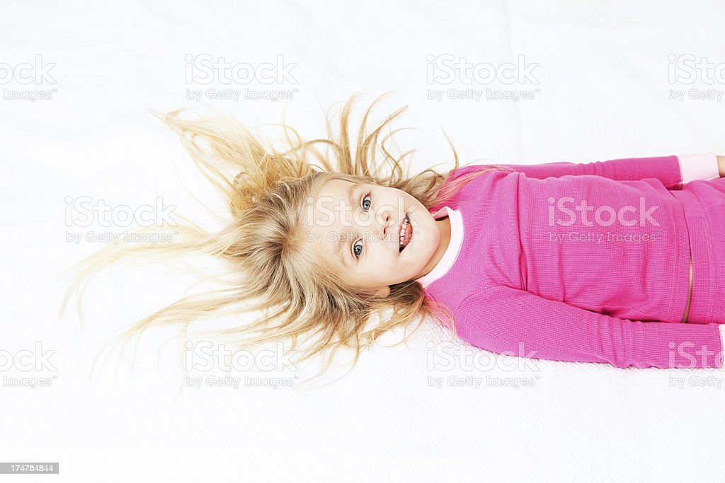 Girl Lying on Bed Sticking out Tongue stock photo
