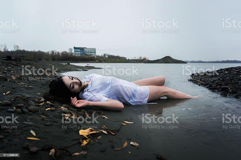 girl lying on dark river stock photo