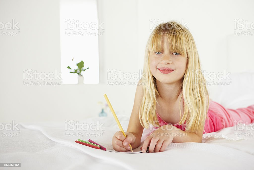 Girl lying on her bed drawing royalty-free stock photo