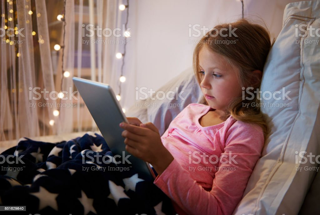 Girl lying on her bed while using a digital tablet stock photo