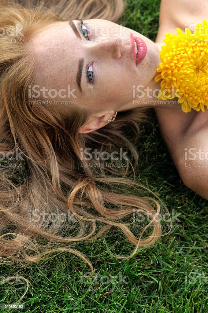 Girl lying on the grass with yellow flowers. stock photo