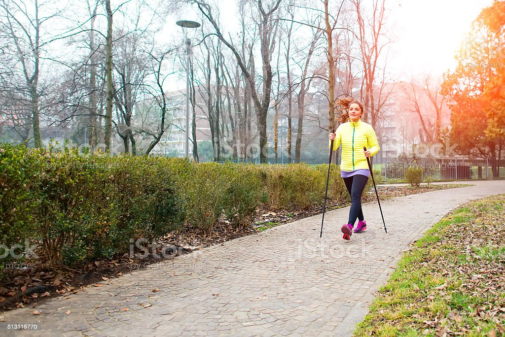 Girl make Nordic walking in the park in the city stock photo