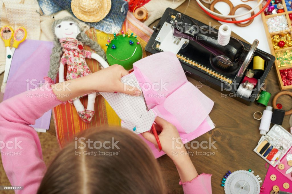 girl makes a dress template, top view, sewing accessories top view, seamstress workplace, many object for needlework, handmade and handicraft stock photo