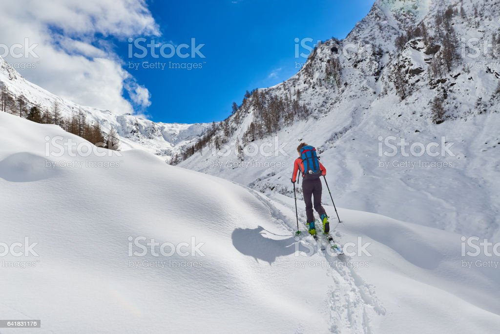 Girl makes ski mountaineering uphill alone stock photo