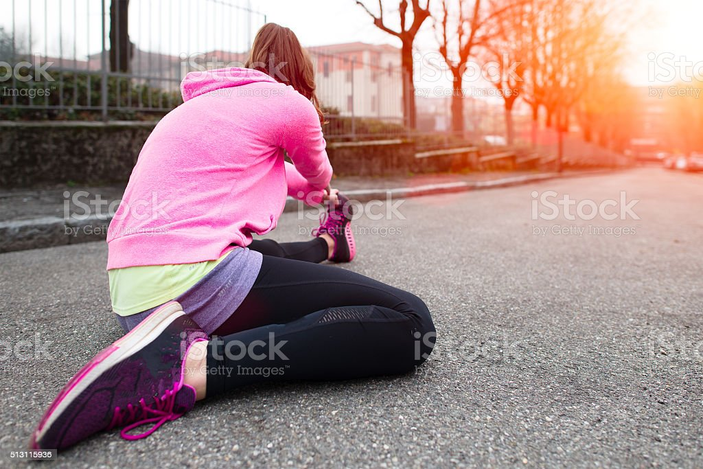 Girl makes stretching in the city dawn stock photo