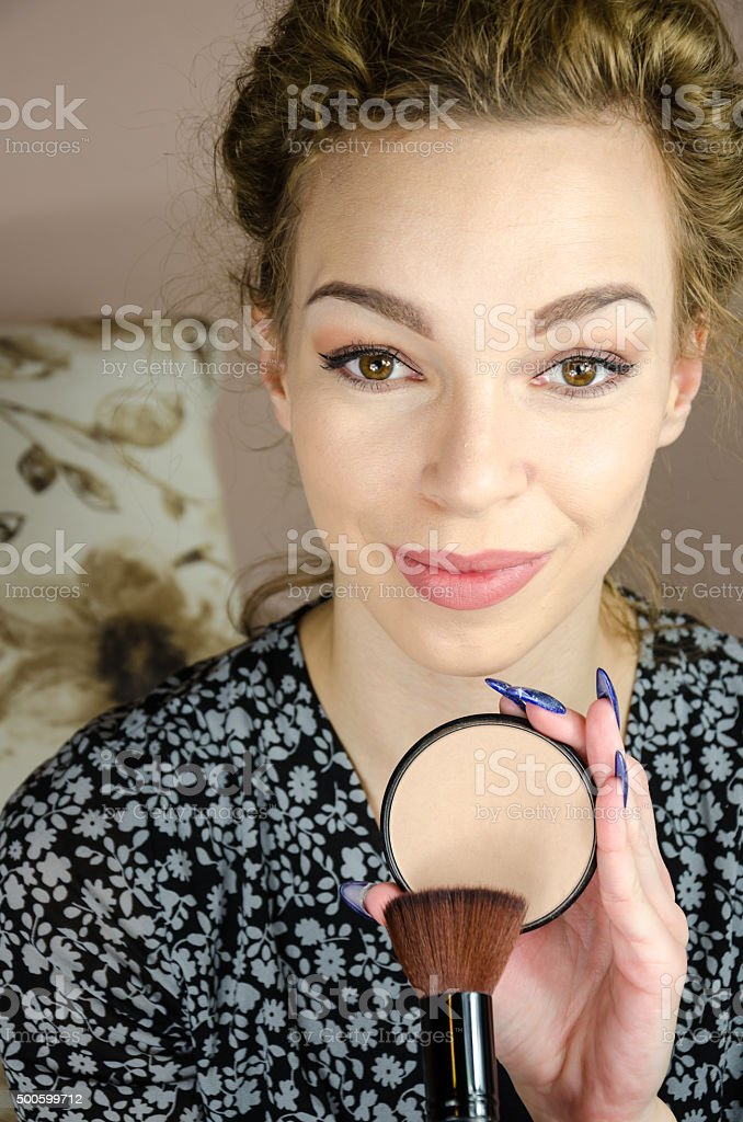 Girl makeup in the mirror and looking into the camera stock photo