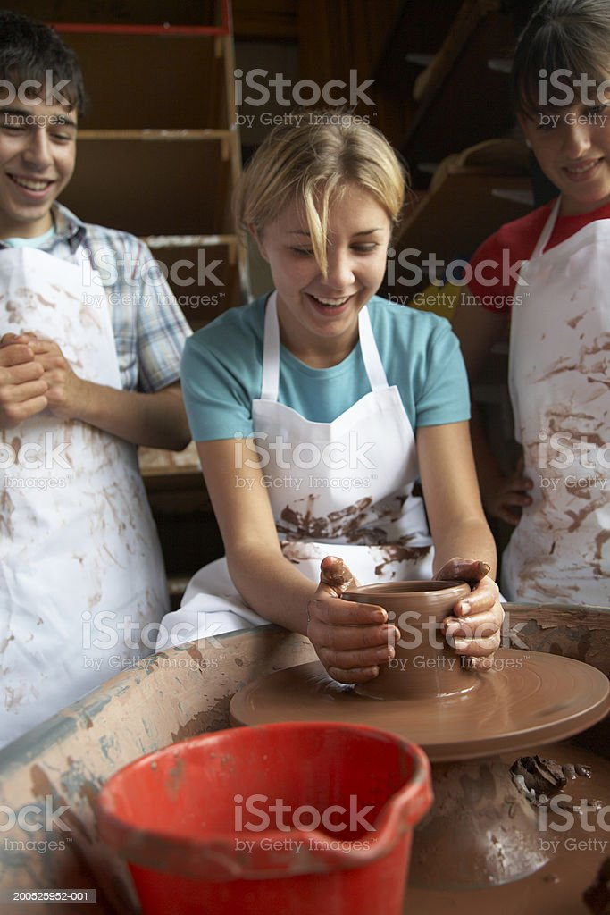 Girl (13-15) making clay pot on wheel in art class, smiling stock photo