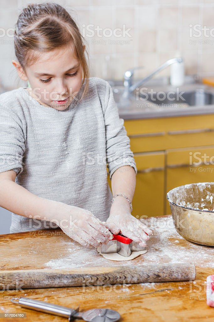 Girl making cutout cookies stock photo