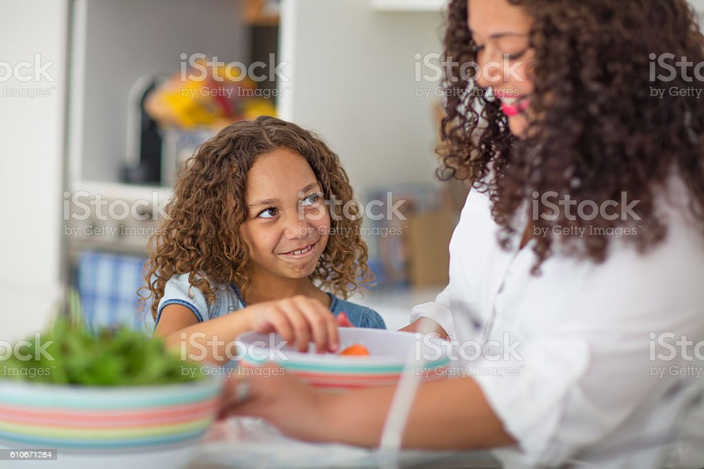 Girl making funny face in kitchen stock photo