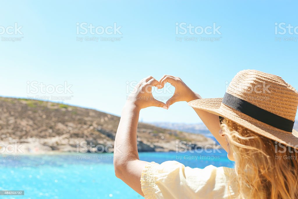 Girl making heart shape on sea cliff stock photo