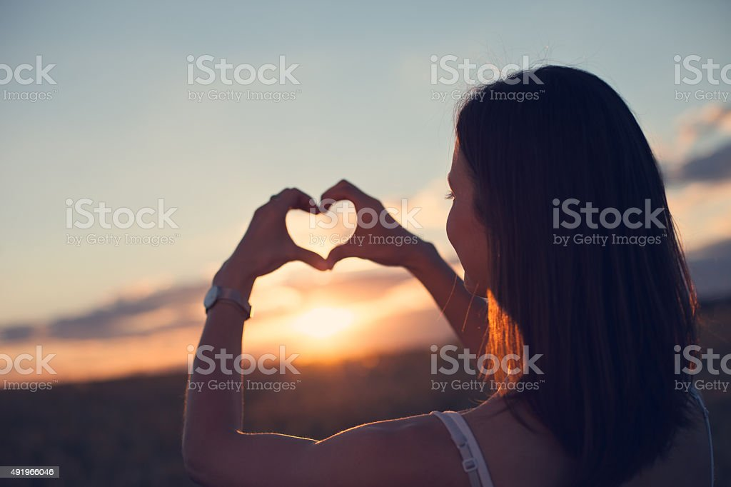 Girl making heart symbol with her hands stock photo