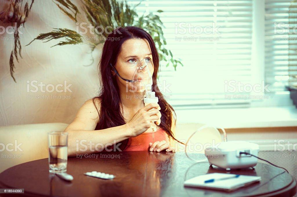 girl making inhalation, breathe through the inhaler treatment of stock photo