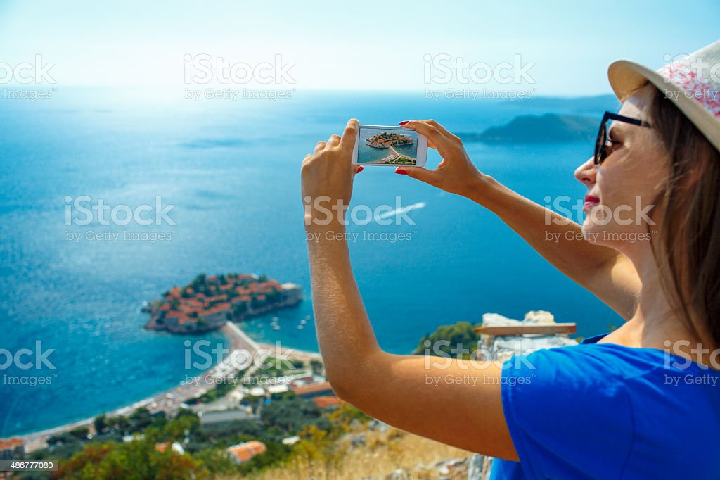 Girl  making photos by the smartphone island of Sveti Stefan stock photo