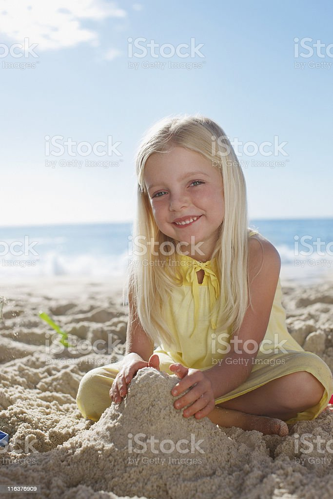 Girl making sandcastle on beach royalty-free stock photo