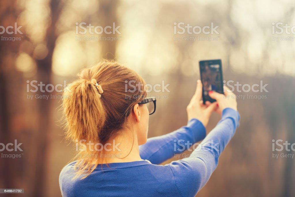 Girl making selfie outdoors in nature / park. stock photo