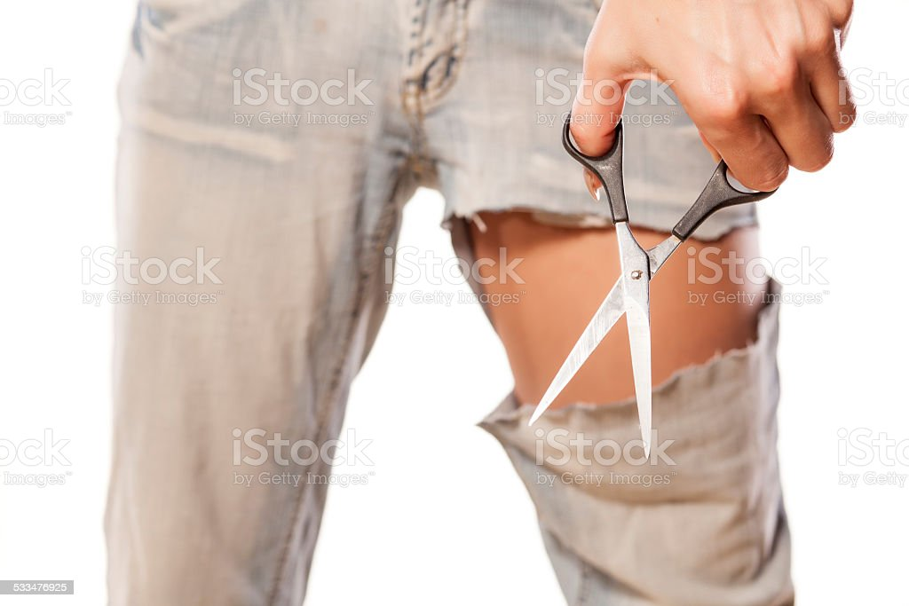Girl making short pants from her old and long jeans stock photo