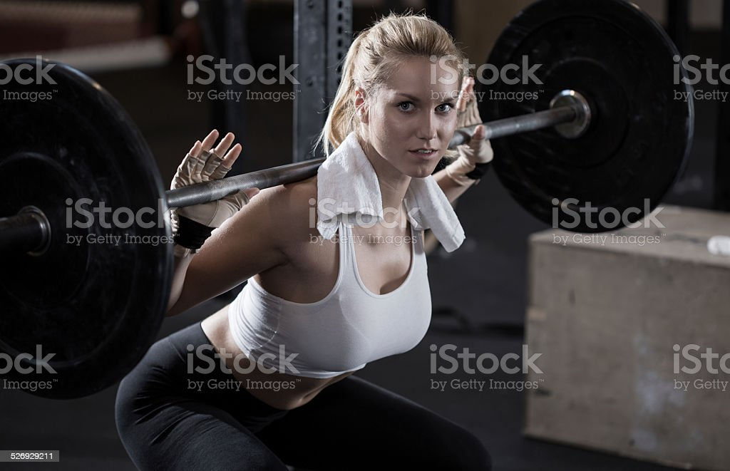 Girl making squat with barbell stock photo