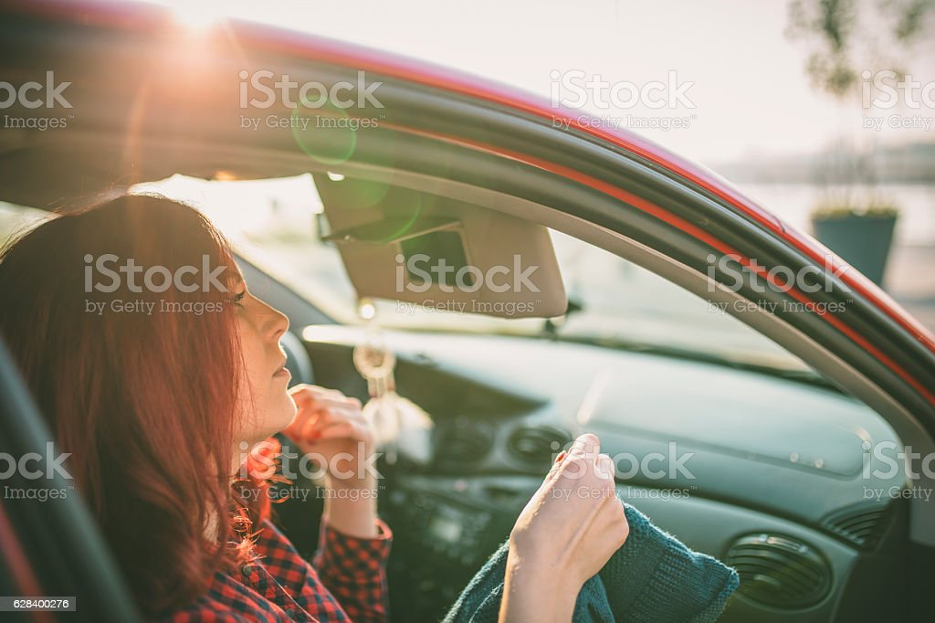 Girl making up into a car. stock photo