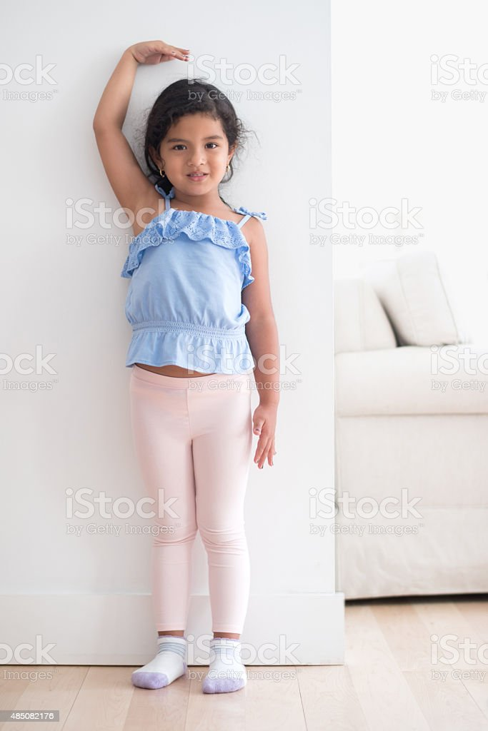 Girl measuring her height against the wall stock photo