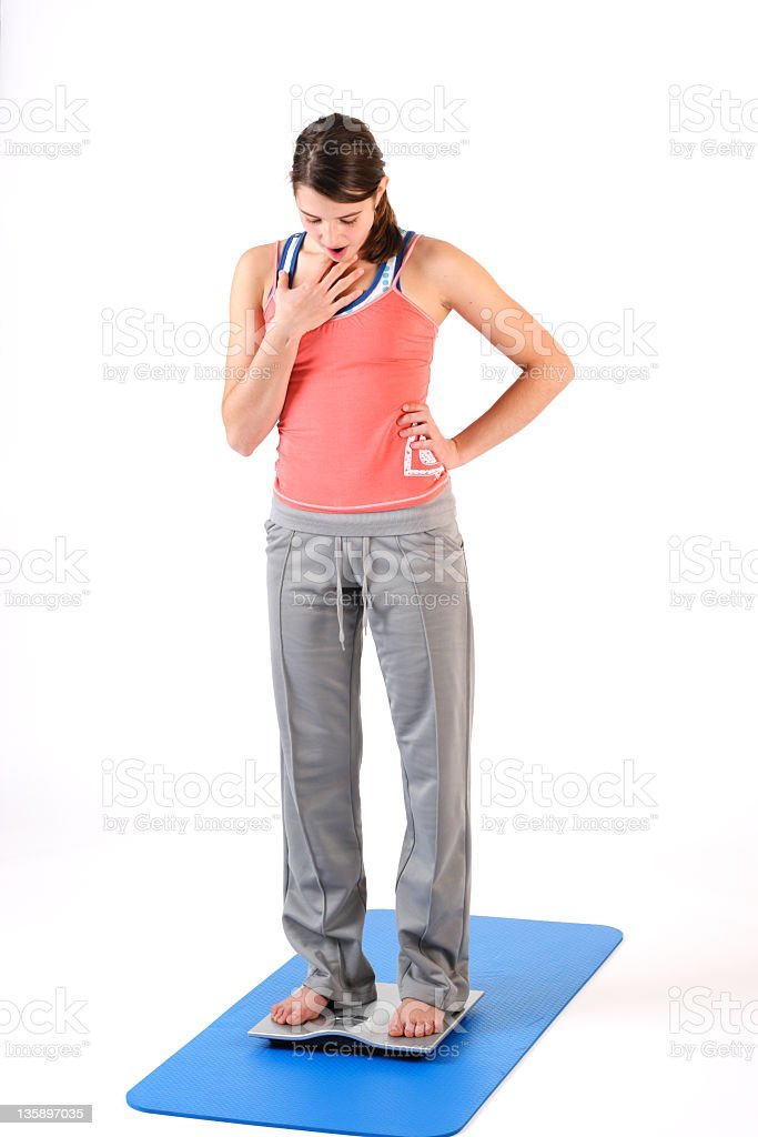 Girl measuring her weight royalty-free stock photo
