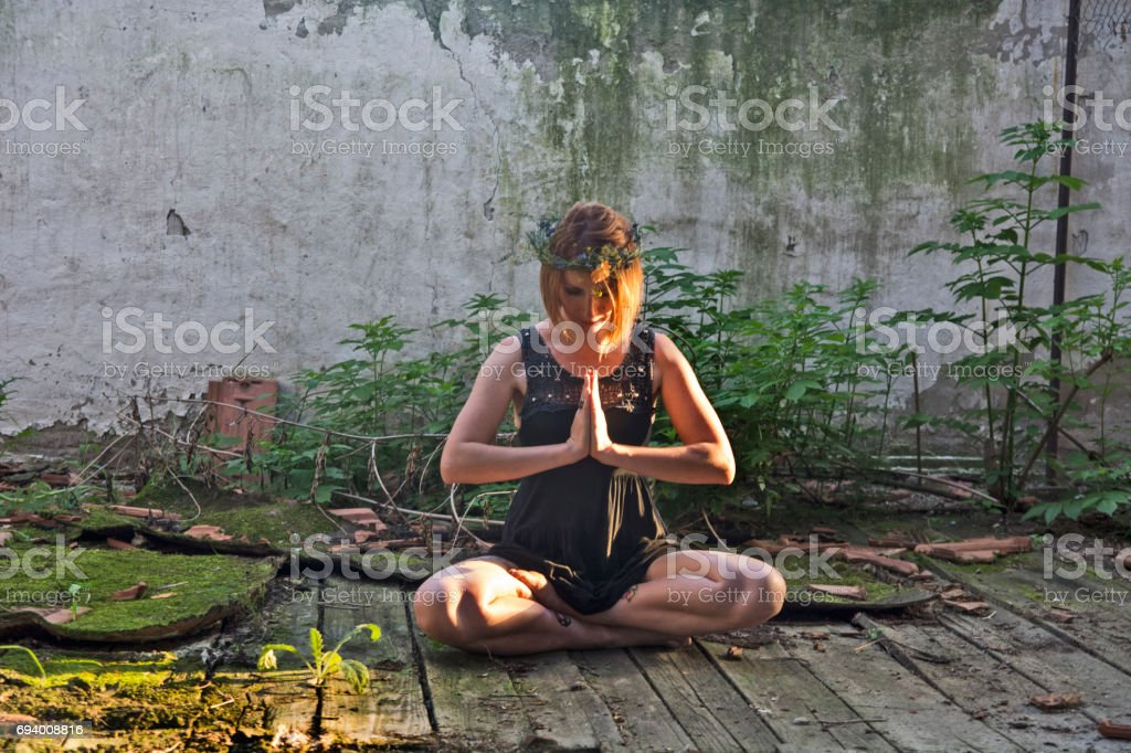 Girl meditating in an old warehouse stock photo