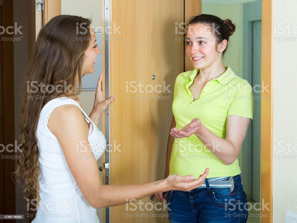 Girl meeting girlfriend at the door stock photo