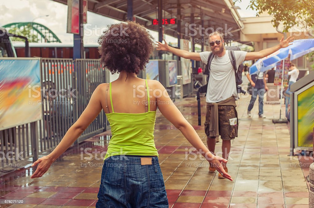 Girl meeting his boyfriend at the bus station stock photo