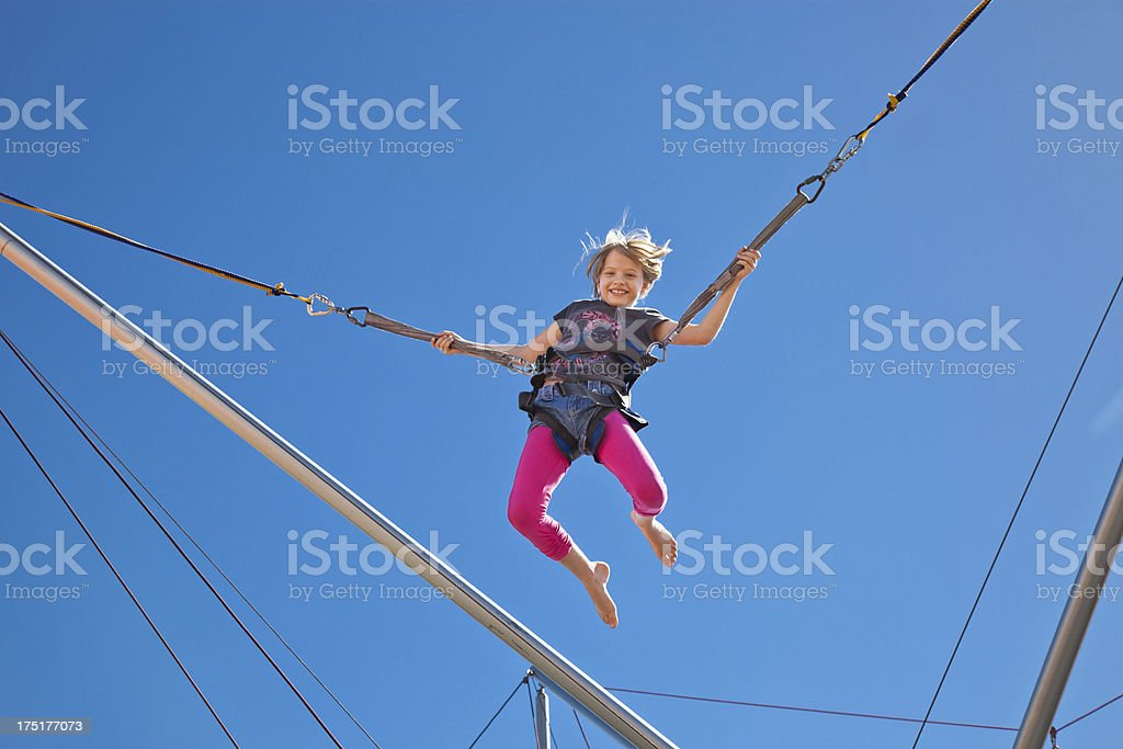 Girl Mid-Air in harness on Bungee Carnival Ride Amusement Park royalty-free stock photo
