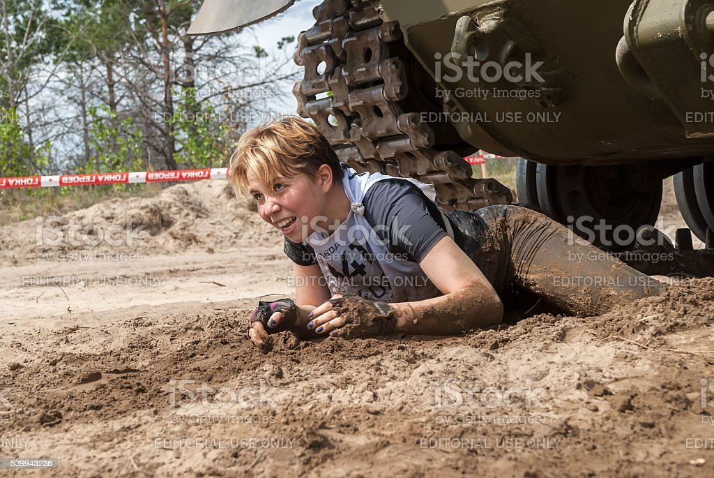 Girl moves under tank in extrim race. Tyumen stock photo