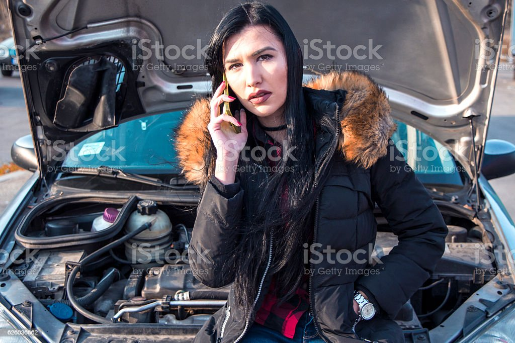 Girl near a broken car is calling for help stock photo